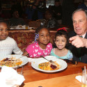 Mayor Michael Bloomberg with homeless children at an annual Christmas Eve lunch for homeless families. Corbis Images.