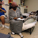 Homeless African American women rest on their cots at the New York Society for Ethical Culture's shelter program. During the evening they wrote in journals, talked, and curled their hair. --- Image by © Viviane Moos/CORBIS